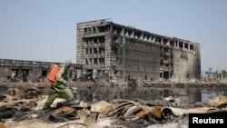 Tentara China menyemprotkan cairan ke arah puing-puing dari ledakan pekan lalu di Tianjin (21/8).