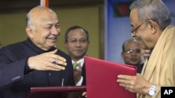 Indian Home Minister Sushilkumar Shinde, left, and his Bangladeshi counterpart Mohiuddin Khan Alamgir prepare to shake hands after signing agreements in Dhaka, Bangladesh, Jan. 28, 2013