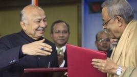 Indian Home Minister Sushilkumar Shinde, left, and his Bangladeshi counterpart Mohiuddin Khan Alamgir prepare to shake hands after signing agreements in Dhaka, Bangladesh, Jan. 28, 2013