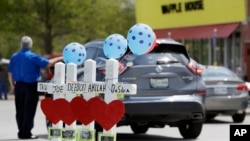 Four wooden crosses stand as a memorial for the four shooting fatalities outside a Waffle House restaurant, April 25, 2018, in Nashville, Tenn. The restaurant re-opened Wednesday after four people were killed by a gunman Sunday.