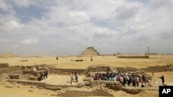 FILE - Archaeologists and journalists are seen at an excavation site in Egypt.