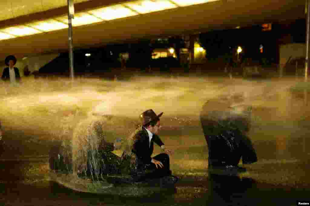 Israeli police use water cannons to disperse ultra-Orthodox Jewish men during a protest against the detention of a member of their community who refuses to serve in the Israeli army, in Jerusalem.
