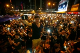 Protesters turn on their mobile phone flashlights as they block an area outside the government headquarters building in Hong Kong Oct. 1, 2014.