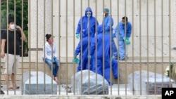 Keluarga dan petugas menunggu giliran untuk memakamkan korban yang diduga meninggal akibat corona di Guayaquil, Ekuador. (Foto: dok).