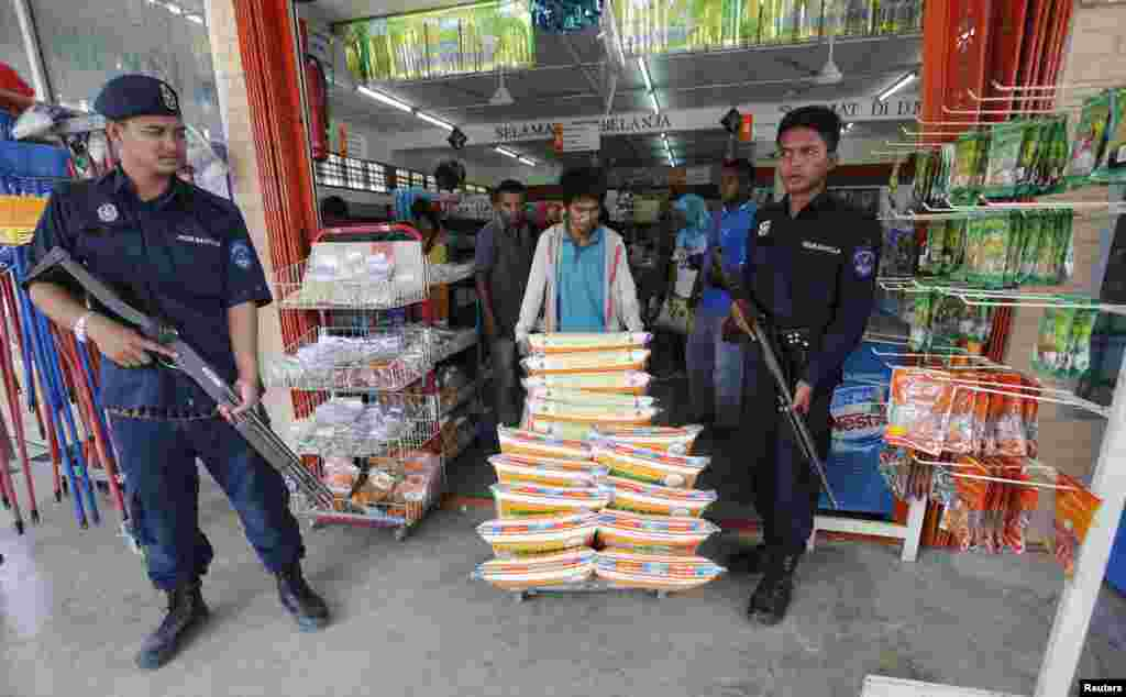 Malaysian police monitor the delivery of goods to a grocery store in Felda Sahabat near where Malaysian troops stormed the camp of an armed Philippine group, March 6, 2013.