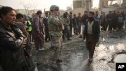 A U.S. soldier, center, takes a photo at the site of a suicide car bomb attack near the headquarters of the European Union police training mission in Kabul, Afghanistan, Jan. 5, 2015.