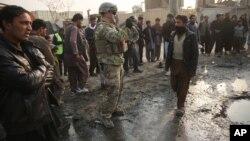 Seorang tentara AS mengambil foto di lokasi serangan bunuh diri di Kabul, Afghanistan (5/1).