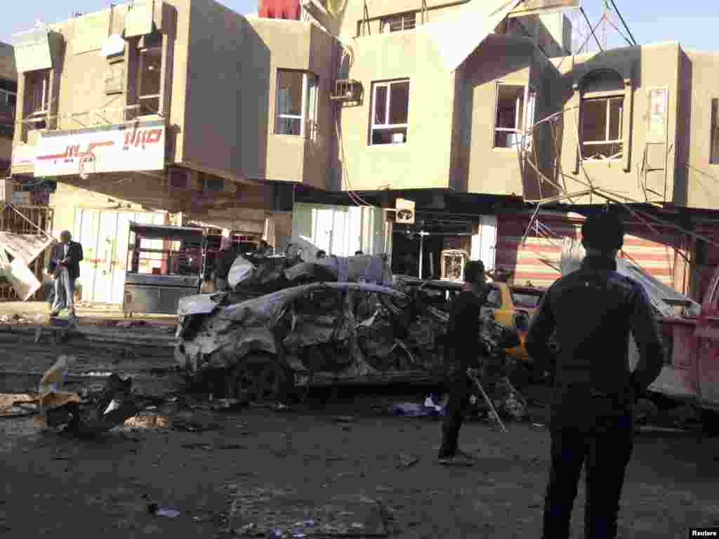 People look at the site of a car bomb attack in Baghdad, Jan. 20, 2014.