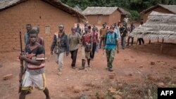 FILE - Anti-Balaka combatants patrol in the parish of Gambo, southeastern Central African Republic, Aug. 16, 2017.