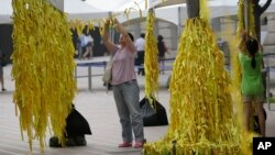 A mother and her daughter tie yellow ribbons with messages for missing passengers and victims aboard the sunken ferry Sewol in the water off the southern coast, at a group memorial altar in Seoul, South Korea, July 28, 2014.