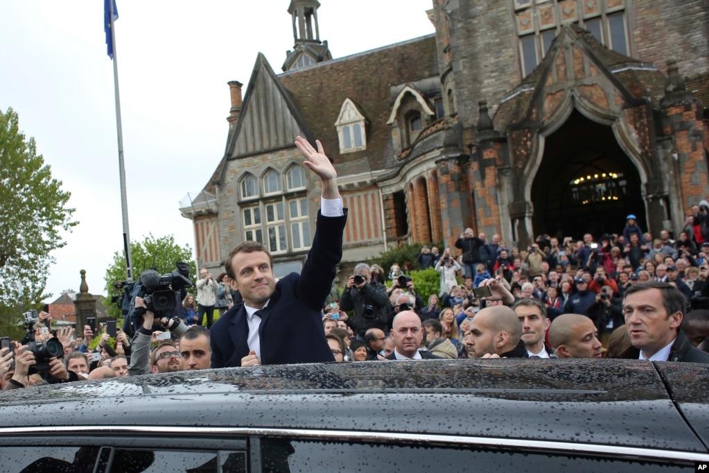 馬克龍在離開投票站時像群眾揮手致意。 5月5日早些時候的民調顯示馬克龍的勢頭增加,並且預測這位親歐盟、親商家的前銀行家和經濟部長將以大約62%比38%的選票戰勝勒龐,獲得大選勝利。