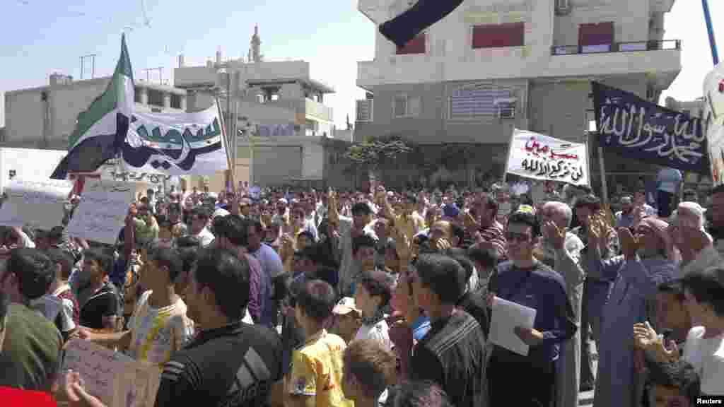 Demonstran berdoa di tengah-tengah aksi protes anti-pemerintah di Sermeen, dekat Idlib, Suriah, Jumat (17/8).