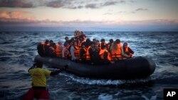 Des réfugiés et migrants arrivent sur un canot à l'île grecque de Lesbos après avoir traversé la mer Egée de la côte turque, 18 décembre 2015.