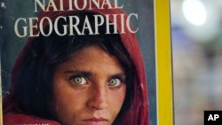 Pakistan's Inam Khan, owner of a book shop shows a copy of a magazine with the photograph of Afghan refugee woman Sharbat Gulla, from his rare collection in Islamabad, Pakistan, Oct. 26, 2016.
