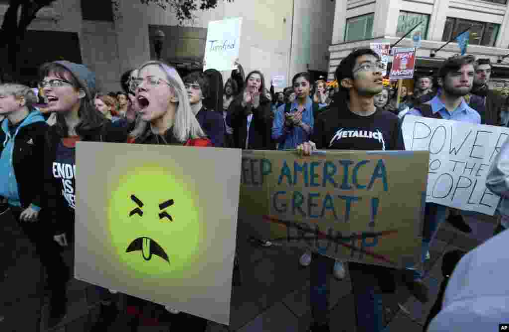 Protesters hold signs during a protest against the election of President-elect Donald Trump, Nov. 9, 2016, in downtown Seattle.
