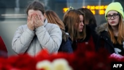 People react, at an entrance of Pulkovo airport during a day of national mourning for the victims of the plane crash, outside St. Petersburg, Russia, Nov. 3, 2015.