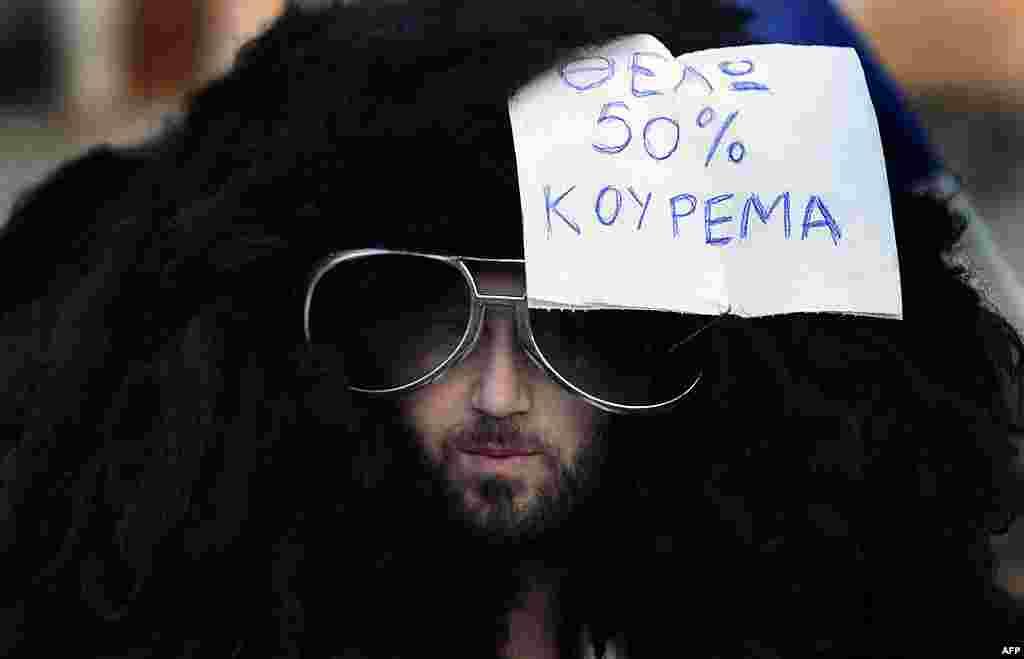 """Một người biểu tình đội bộ tóc giả có tờ giấy đi kèm ghi câu """"Tôi cần giảm giá cắt tóc 50%"""" ,bên ngoài trụ sở Quốc hội ở Athens, 19 tháng 2, 2012. (Reuters)"""