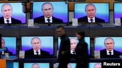 Arhiva - Posetilac hoda pored TV ekrana tokom obraćanja predsednika Vladimira Putina naciji i odgovaranja na telefonska pitanja, ispred izloga radnje za elektronskom opremom u sibirskom gradu Krasnojarsk, Rusija, 17. aprila 2014.
