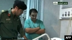 Ðài truyền hình nhà nước Libya chiếu hình ảnh ông Khamis Gadhafi (trái) đang đi thăm những người Libya bị thương tại một bệnh viện