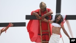 Voluntario vestidos como centuriones romanos ayudan a bajar a Rubén Enaje, después de que fuera clavado en la cruz durante la conmemoración del Viernes Santo en las Filipinas.