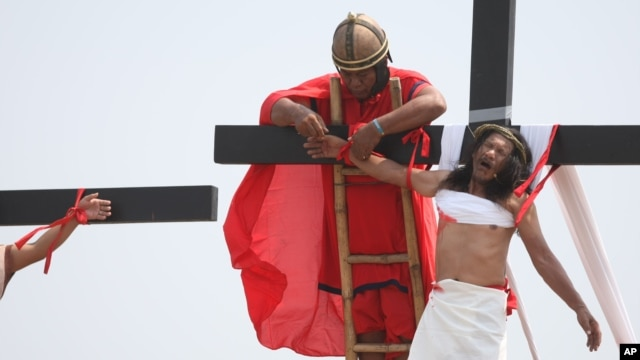 A volunteer dressed as a Roman centurion unties Ruben Enaje's wrist after he was nailed to a wooden cross during a Good Friday re-enactment in Cutud, Pampagna province, northern Philippines, March 25, 2016.