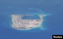 FILE - Chinese dredging vessels are purportedly seen in the waters around Fiery Cross Reef in the disputed Spratly Islands in the South China Sea in this still image from video taken by a P-8A Poseidon surveillance aircraft provided by the United States N