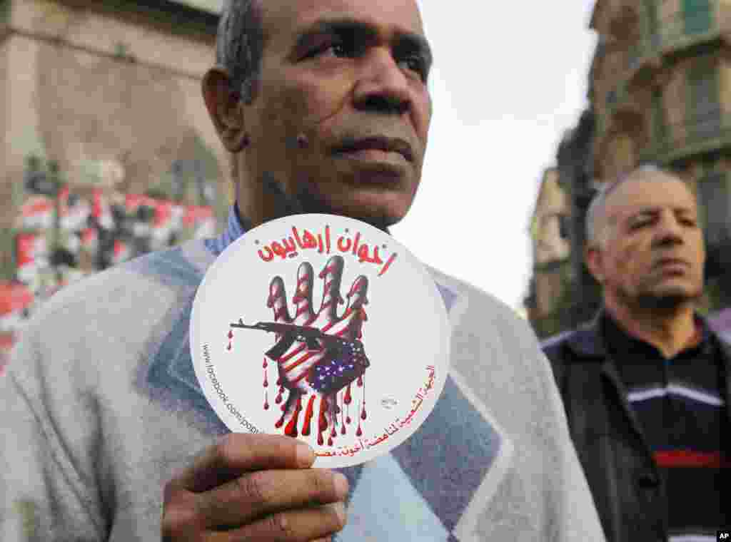 """An activist holds a sign with an anti-terrorism picture and Arabic that reads """"terrorists brotherhood"""" during an anti-terrorism demonstration in Cairo, Dec. 26, 2013."""