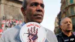 """Egipatski aktivista nosi poruku """"Terorističko bratstvo"""" na demonstracijama protiv terorizma održanim u Kairu 26. decembra 2013."""