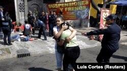 Seorang perempuan menenangkan temannya setelah seorang kerabat ditembak orang tak dikenal di luar bengkel di Mexico City, Meksiko, 12 Februari 2021.(Foto: Luis Cortes/Reuters)