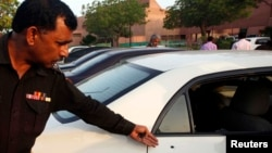 A policeman points out bullet hole in car belonging to journalist Hamid Mir in Karachi, Apr. 19, 2014.
