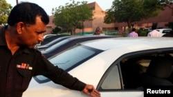 Policajac pokazuje rupu od metka na automobilu novinara Hamida Mira, parkiranom kod bolnice u Karaciju, 19. aprila 2014.