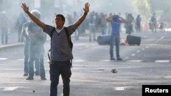 Un manifestante camina entre el humo de los gases lacrimógenos lanzados por las fuerzas de seguridad venezolanas.