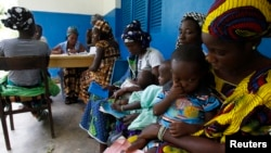 Women holding children wait for a medical examination at the health center in Gbangbegouine village, western Ivory Coast, July 4, 2013.