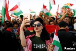 A Kurdish woman takes a selfie to show support for the upcoming September 25th independence referendum in Irbil, Iraq Sept. 22, 2017.