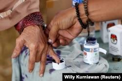Seorang petugas pemilu membantu seorang perempuan lanjut usia untuk menandai jarinya dengan tinta setelah memberikan suaranya pada Pilkada di Tangerang, Banten, 27 Juni 2018. (Foto: REUTERS/Willy Kurniawan)