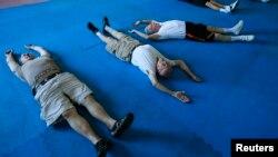 چند بیمار مبتلا به پارکینسون در حال تمرین با مربی شان.