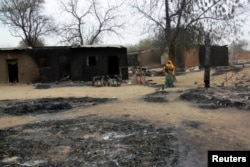 A woman carrying a child stands near burnt houses in the aftermath of what Nigerian authorities said was heavy fighting between security forces and Islamist militants in Baga, a fishing town on the shores of Lake Chad, April 21, 2013.