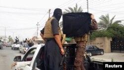 Chiến binh của nhóm ISIL ăn mừng sau khi chiếm được xe cộ của lực lượng an ninh Iraq trên đường phố Mosul, ngày 12/6/2014.