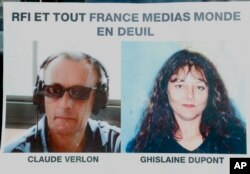 "Pictures of French RFI journalists, Ghislaine Dupont and Claude Verlon on a poster headed ""RFI and all France Media World in Mourning"" displayed in a window in Paris, Nov. 3, 2013."