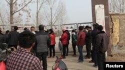 Warga setempat berdiri di luar komplek tambang yang roboh di provinsi Shandong, China timur Jumat (25/12).
