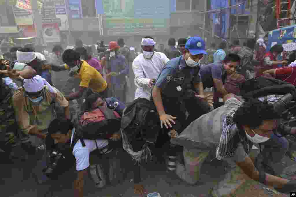 Bangladeshi rescue workers and media fall on top of each other in a stampede after the crowd panicked when someone shouted a section of building might collapse, at the site of a building that collapsed on Apr. 24, 2013, in Savar, near Dhaka.