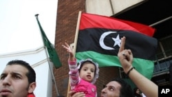 一群利比亞人星期三在津巴布韋首都哈拉雷市中心的利比亞大使館外面舉行示威。