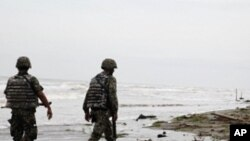 Navy officers walk along El Bosque beach, in Mexico's Tabasco state, Saturday, Sept. 10, 2011