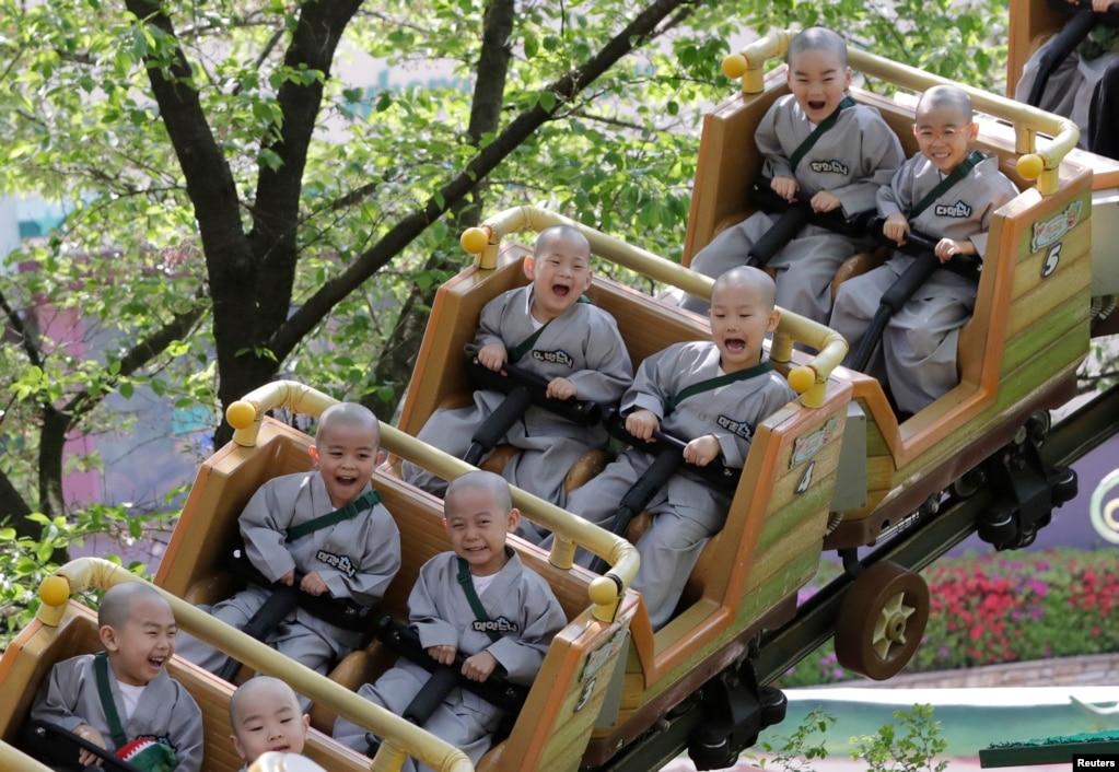 Дети-монахи катаются на американских горках во время посещения парка развлечений Everland в Йонгине, Южная Корея.