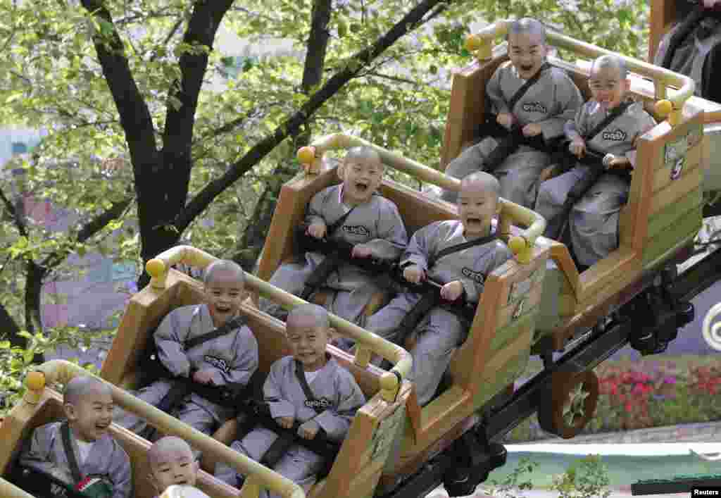 Young monks ride a roller coaster during their visit to the Everland amusement park in Yongin, South Korea.