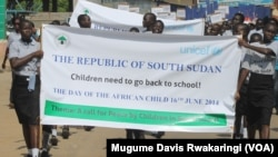 A poster carried by South Sudanese children in Juba on Monday, June 16, 2014, the Day of the African Child, asks for the right to go to school.
