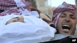 ຜູ້ຊາຍຊາວຊີເຣຍຄົນນຶ່ງ ຮ້ອງຄຳຂວັນ ຕໍ່ຕ້ານລັດຖະບານ ຂະນະທີ່ຫາມສົບນາຍ Abdulaziz Abu Ahmed Khrer ທີ່ເສຍຊີວິດຍ້ອນຖືກມືປືນລັດຖະບານຊີເຣຍຍິງຕາຍ ໃນພິທີສົ່ງສະການ ທີ່ເມືອງ Idlib (8 ມີນາ 2012)