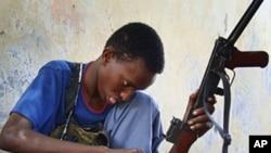 ایک صومالی جنگجو اپنی اے کے ۴۵ صاف کر رہا ہے