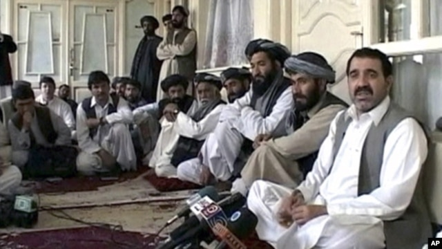 Kandahar provincial governor Ahmad Wali Karzai (R), a brother of Afghan President Hamid Karzai, talks to journalists in Kandahar in this still image taken from a April 2009 video.
