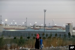 FILE - A woman and a boy walk outside a high security prison complex in Silivri, about 80 kilometers (50 miles) west of Istanbul, Aug. 17, 2016. Turkey abolished the death penalty in 2004 as part of its bid to join the European Union. Reinstating it would deal a fatal blow to its EU ambitions.